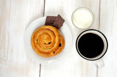 Simple Breakfast: bun roll with raisins, chocolate and coffee  Royalty Free Stock Image