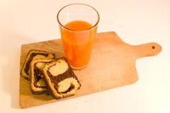 Simple breakfast chocolate roll with carrot juice Royalty Free Stock Photography