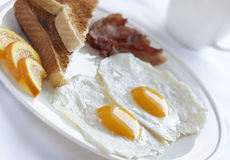 Simple breakfast egg. Healthy breakfast with egg,bacon and toast on a white plate with very shallow depth of field Royalty Free Stock Image