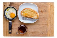 Simple breakfast with fried egg, toast and tea. Simple breakfast with seasoned fried egg in a small frying pan, toast and mug of hot tea served on a wooden Royalty Free Stock Photo