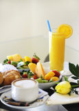 Simple breakfast room service delivery. Vertical shot of continental breakfast with fruit salad and orange juice in glassware, with coffee with milk and fresh stock image