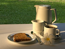 Simple Breakfast of Toast & Coffee. A pot of coffee, cream, toast and a frangipani flower in an outdoor garden setting stock images