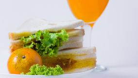 Simple breakfast in white plate, sandwich, oranges and fruit juice.  royalty free stock photo