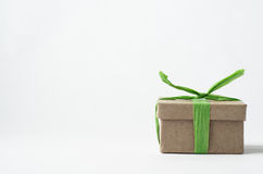 Simple Brown  Gift Box Tied with Green Raffia Ribbon. Eye level shot of simple brown gift box in lower right of frame with closed lid, tied with light green Stock Photos