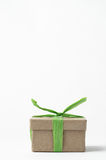 Simple Brown Gift Box Tied Up with Green Raffia Ribbon. Simple brown gift box with lid, tied to a top knot with light green raffia ribbon Royalty Free Stock Photography