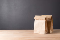 Simple brown paper bag for lunch or food on table. Simple brown paper bag for lunch or food on wooden table with copy space royalty free stock photo