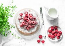 Simple butter cake with raspberry on light background, top view. Delicious summer dessert. Stock Photography