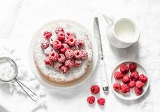 Simple cake with powdered sugar and fresh raspberries on a light background. Summer berry dessert. Flat lay royalty free stock images