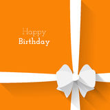 Simple card for birthday with a white paper bow on orange background Stock Photography