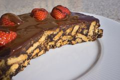 Simple chocolate cake, pie or flan made from quality chocolate english style bisquits and fresh raw strawberries. Served on the white simple plate. Cut of piece Stock Image