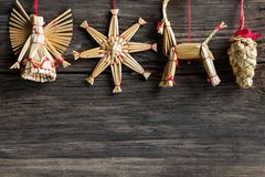 Simple Christmas background - straw ornaments hanging over a woo royalty free stock photos