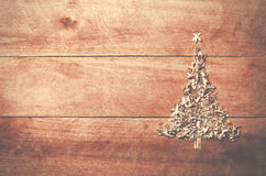 Simple Christmas tree arranged from sawdust, wood-chips on wooden background. stock images