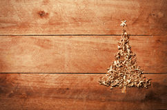Simple Christmas tree arranged from sawdust, wood-chips on woode. N background Royalty Free Stock Photos