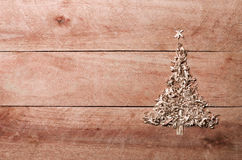 Simple Christmas tree arranged from sawdust, wood-chips on wooden background Stock Image
