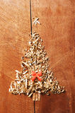 Simple Christmas tree arranged from sawdust, wood-chips on wooden background. Orange cute ribbon Royalty Free Stock Photo