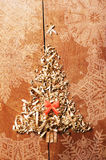Simple Christmas tree arranged from sawdust, wood-chips on wooden background. Orange cute ribbon Stock Photos
