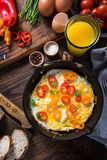 Simple classic brunch. Scrambled eggs in rustic pan on wooden table Stock Photography