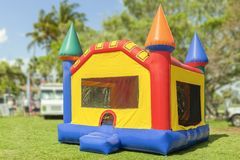 A simple but colorful castle bounce house. The inflated bounce house with pops of color sits at the park on a beautiful sunny day stock images