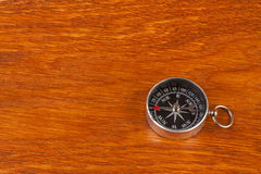 Simple compass on brown wood surface Royalty Free Stock Photography