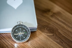 Simple compass over the book on the wooden table with copy space Royalty Free Stock Photography
