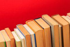 Simple composition of hardback books, raw of books on wooden deck table and red background - Image. Simple composition of hardback books, raw of books on wooden stock image