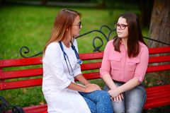Simple conversation. caring doctor or nurse taking young patient. Caring doctor or nurse taking young patient outdoors, sitting on a bench hold conversation stock photography
