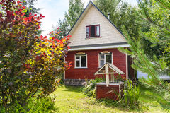 Simple cottage and well on backyard in village Stock Photos