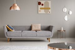 Simple couch with pillows in a living room decorated with copper lamp, mirror and painting. Real photo of a simple couch with pillows in a living room decorated royalty free stock photos