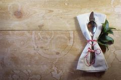 Simple country Christmas place setting on genuine rustic wood table with holly leaves. Horizontal aspect Royalty Free Stock Photography