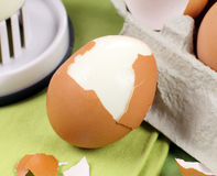 Simple Cracked Egg. Cracked brown egg with egg carton and slicer Royalty Free Stock Images