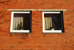 Simple cute windows. The red brick wall with the bars on windows Royalty Free Stock Images