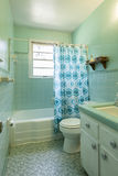 Simple dated 1950s bathroom with green tile. stock photo