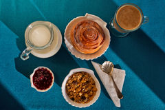 Simple and delicious breakfast laid on the aquamarin tablecloth. This delicious breakfast made in shell-like crockery consists of muesli, cinnamon roll. ja, and royalty free stock images