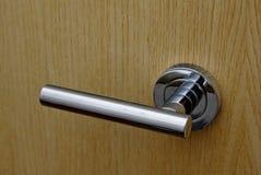 Simple design modern door handle. Closeup of a simple design minimalistic door handle on a wood texture door Royalty Free Stock Image