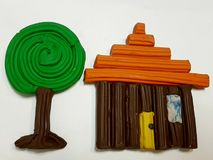 Simple design of a wooden house and a tree with plasticine. School material, background and texture, colors and shape Royalty Free Stock Photos