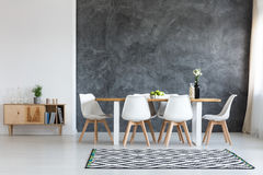 Simple dining room. White flowers in black vase next to glass container with wine corks on dining table Royalty Free Stock Photo