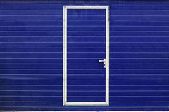 Simple door in blue wall Stock Image