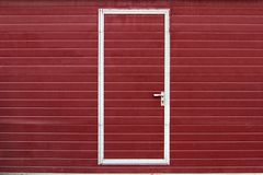 Simple door in red wall Stock Images