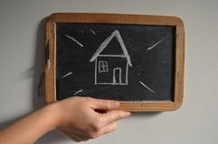 Simple drawing concept new house or home. A childlike drawing of a new house on blackboard with white background Stock Images