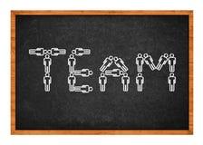 Team figures. Simple drawing of people figures forming word TEAM on school blackboard Royalty Free Stock Images