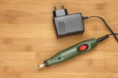 Rotary tool and power supply. Simple Dremel type rotary tool and power supply on a light wooden bamboo background Stock Images