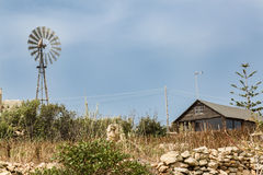 Simple dwelling with a wind turbine Stock Image