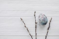 Simple easter egg with floral ornaments and willow buds on rusti. C white wooden desk background. happy easter greeting card concept with space for text, top Royalty Free Stock Photography