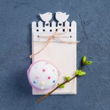 Simple Easter holiday composition of decorated cupcake, branch with young shoots of greenery and handcraft notebook with empy blan. K on dark stone background Stock Photos