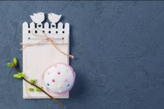 Simple Easter holiday composition of decorated cupcake, branch with young shoots of greenery and handcraft notebook with empy blan. K on dark stone background Royalty Free Stock Photography