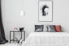 Elegant bedroom with wall molding. Simple, elegant bedroom interior with silver cushions on white bed standing against a wall with molding Stock Photo