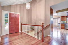 Simple entry way with hardwood floor and staircase. Stock Photography
