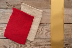 Simple fabric gift bags, golden ribbon on plain wooden background. Simple fabric gift bags, golden ribbon Stock Photography