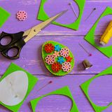 Simple felt Easter egg decor. Handmade felt Easter egg with colored wooden buttons. Felt scrap, scissors, thimble, thread. Simple handmade toy. How to hand sew a Stock Image
