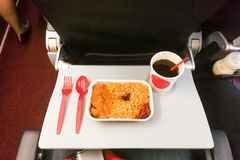 Simple in-flight meal of rice, meat, coffee in disposable utensi. Simple in-flight prepared meal of rice, meat, coffee in disposable utensils Royalty Free Stock Images